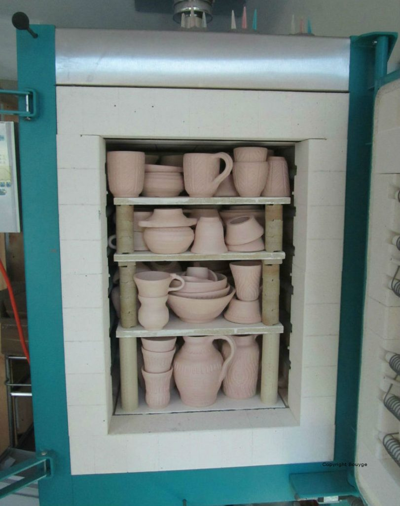 Four de Poterie , porte ouverte, avec emilement de pièces dégourdies après première cuisson