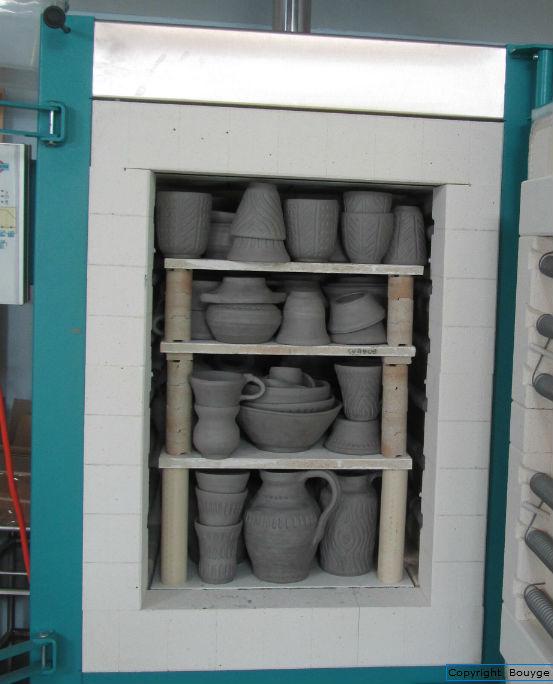 Four de Poterie, porte ouverte, avec un empilement de pièces crues et sèches prêt à cuire