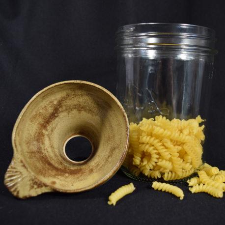 Entonnoir jaune ancien avec marbrures posé à côté d'un bocal contenant des pâtes