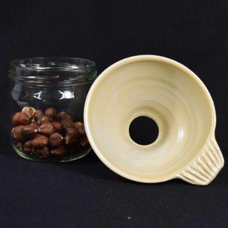 Entonnoir à confiture beige posé près d'un bocal contenant des noisettes