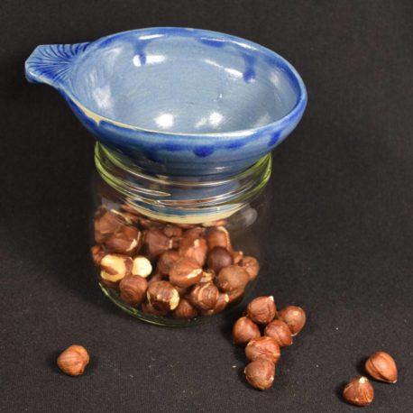 Entonnoir bleu Majorelle posé sur un bocal contenant des noisettes