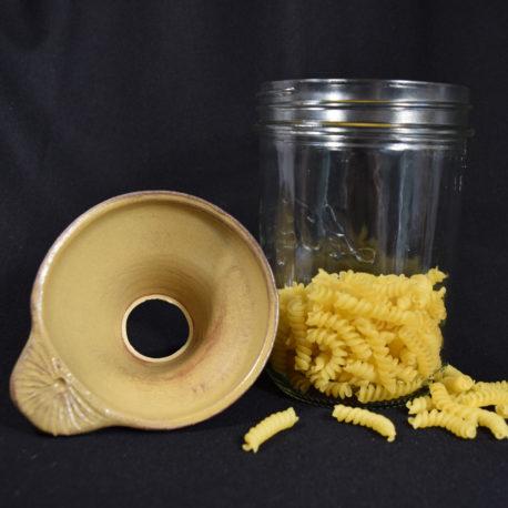 Entonnoir jaune ancien de couleur uniforme posé à côté d'un bocal contenant des pâtes