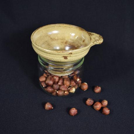 Entonnoir jaune ancien posé sur un pot contenant des noisettes.