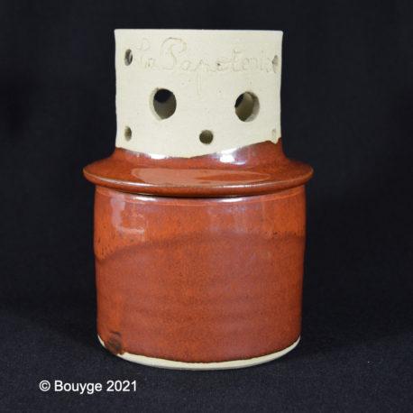 Beurrier à eau de couleur rouge avec couvercle posé côté ouvert sur le dessus