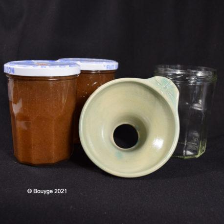 Entonnoir à confiture vert clair posé à côté de pots de confiture